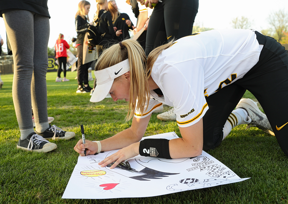 Iowa's Aralee Bogar (2) signs a poster for a fan after winning their game against Ohio State at Pearl Field in Iowa City on Friday, May. 3, 2019. (Stephen Mally/hawkeyesports.com)