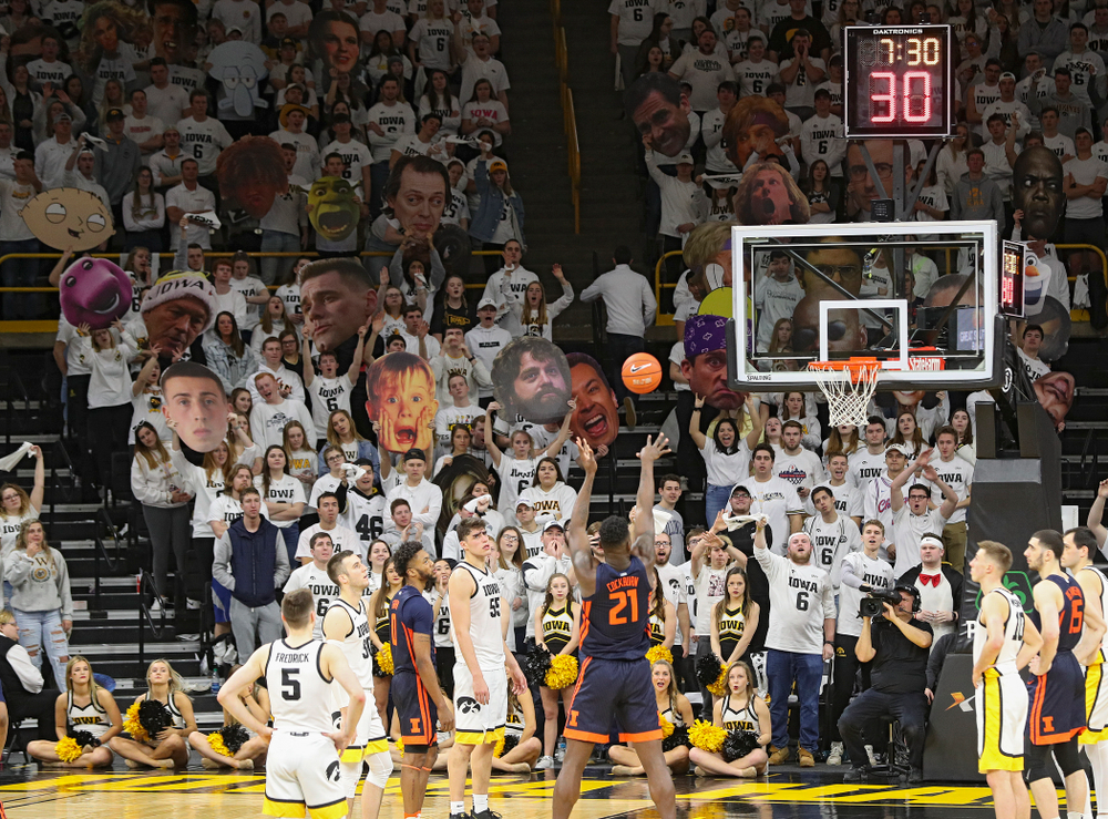 Students in the Hawks Nest hold up heads to distract an Illinois player shooting a free throw during the second half of the game at Carver-Hawkeye Arena in Iowa City on Sunday, February 2, 2020. (Stephen Mally/hawkeyesports.com)
