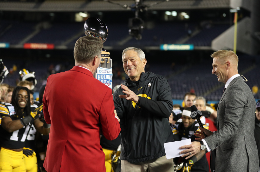Iowa Hawkeyes head coach Kirk Ferentz is presented with the Holiday Bowl trophy following their win against USC in the Holiday Bowl Friday, December 27, 2019 at San Diego Community Credit Union Stadium.  (Brian Ray/hawkeyesports.com)