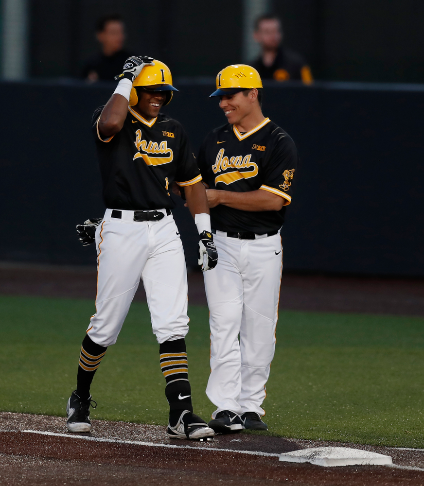 Iowa Hawkeyes third baseman Lorenzo Elion (1) and volunteer coach Sean Moore against Milwaukee Wednesday, April 25, 2018 at Duane Banks Field. (Brian Ray/hawkeyesports.com)
