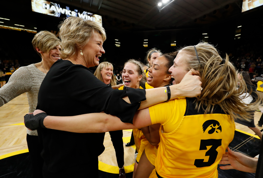 Iowa Hawkeyes head coach Lisa Bluder, guard Makenzie Meyer (3), guard Alexis Sevillian (5), and guard Kathleen Doyle (22)