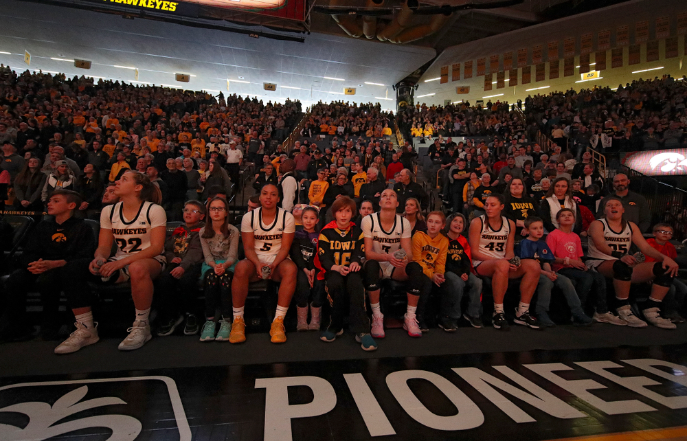 Iowa Hawkeyes guard Kathleen Doyle (22), guard Alexis Sevillian (5), guard Makenzie Meyer (3), forward Amanda Ollinger (43), and forward Monika Czinano (25) sit on the bench with Go Red for Women Movement Heart Champions before being introduced at the start of their game at Carver-Hawkeye Arena in Iowa City on Sunday, January 26, 2020. (Stephen Mally/hawkeyesports.com)