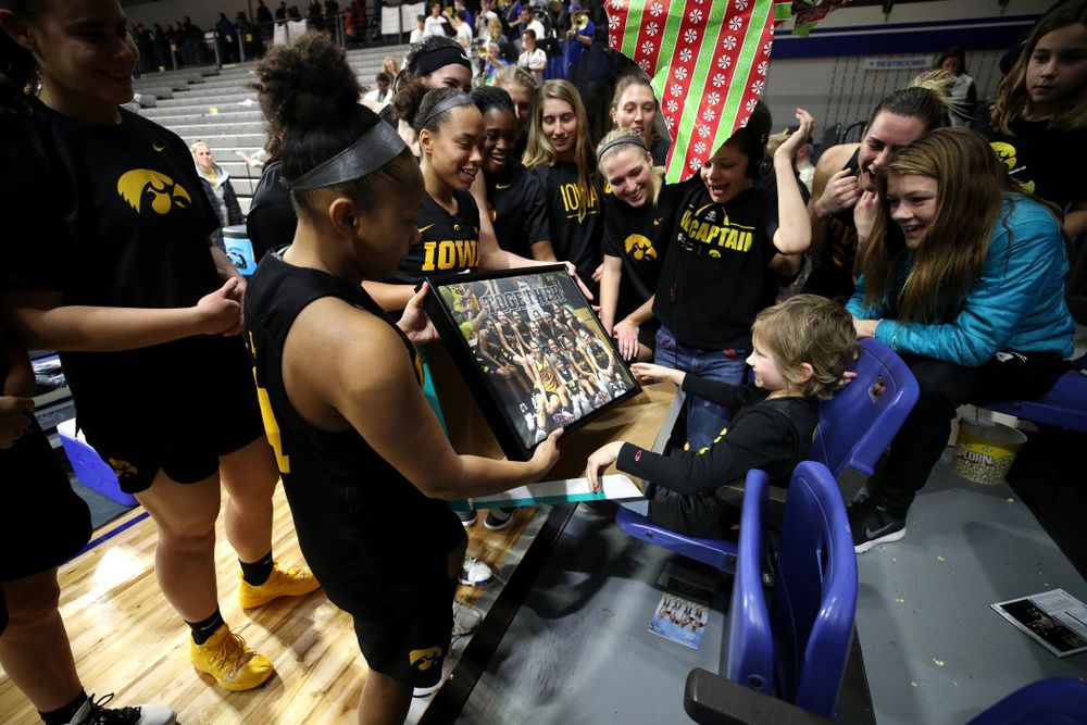 The Iowa Hawkeyes present their adopted team member Harper Stribe a photo for Christmas following their win over the Drake Bulldogs Friday, December 21, 2018 at the Knapp Center in Des Moines. (Brian Ray/hawkeyesports.com)