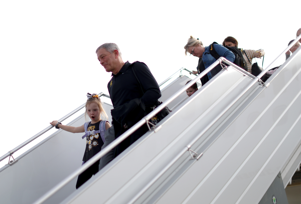Iowa Hawkeyes head coach Kirk Ferentz disembarks the team plane with his grand daughter after arriving in San Diego, CA Saturday, December 21, 2019 for the Holiday Bowl. (Brian Ray/hawkeyesports.com)
