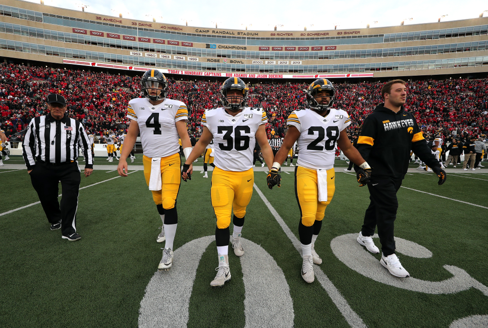 Iowa Hawkeyes captains quarterback Nate Stanley (4), fullback Brady Ross (36), running back Toren Young (28), and linebacker Kristian Welch (34) walk out for the coin toss against the Wisconsin Badgers Saturday, November 9, 2019 at Camp Randall Stadium in Madison, Wisc. (Brian Ray/hawkeyesports.com)