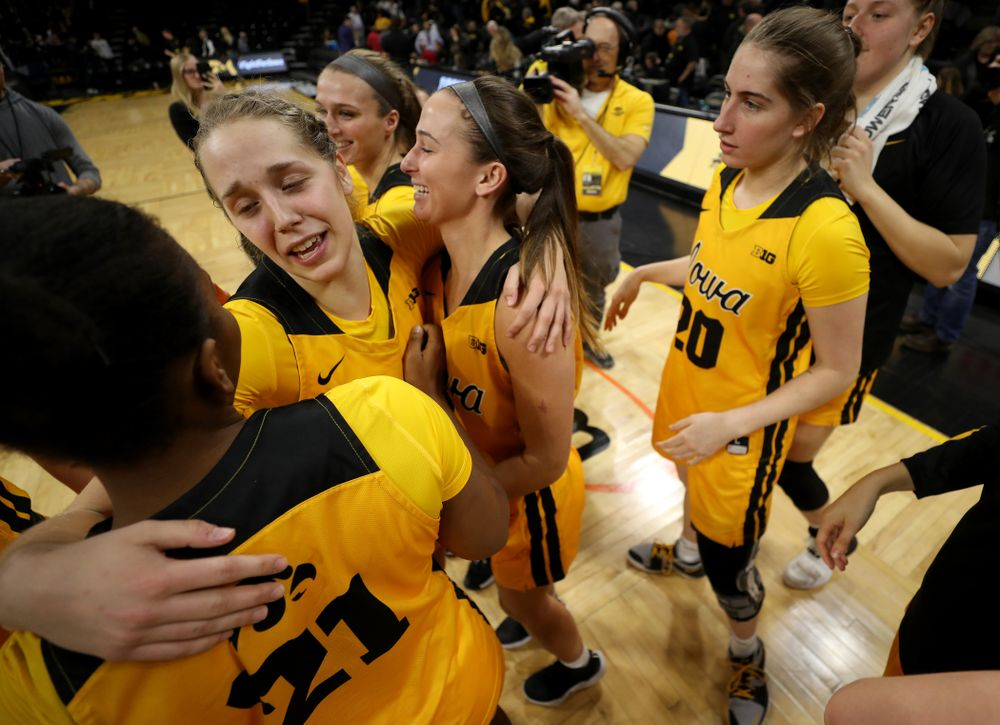 Iowa Hawkeyes guard Kathleen Doyle (22) hugs guard Megan Meyer (11) and guard Zion Sanders (21) during senior day activities following their win over the Minnesota Golden Gophers Thursday, February 27, 2020 at Carver-Hawkeye Arena. (Brian Ray/hawkeyesports.com)