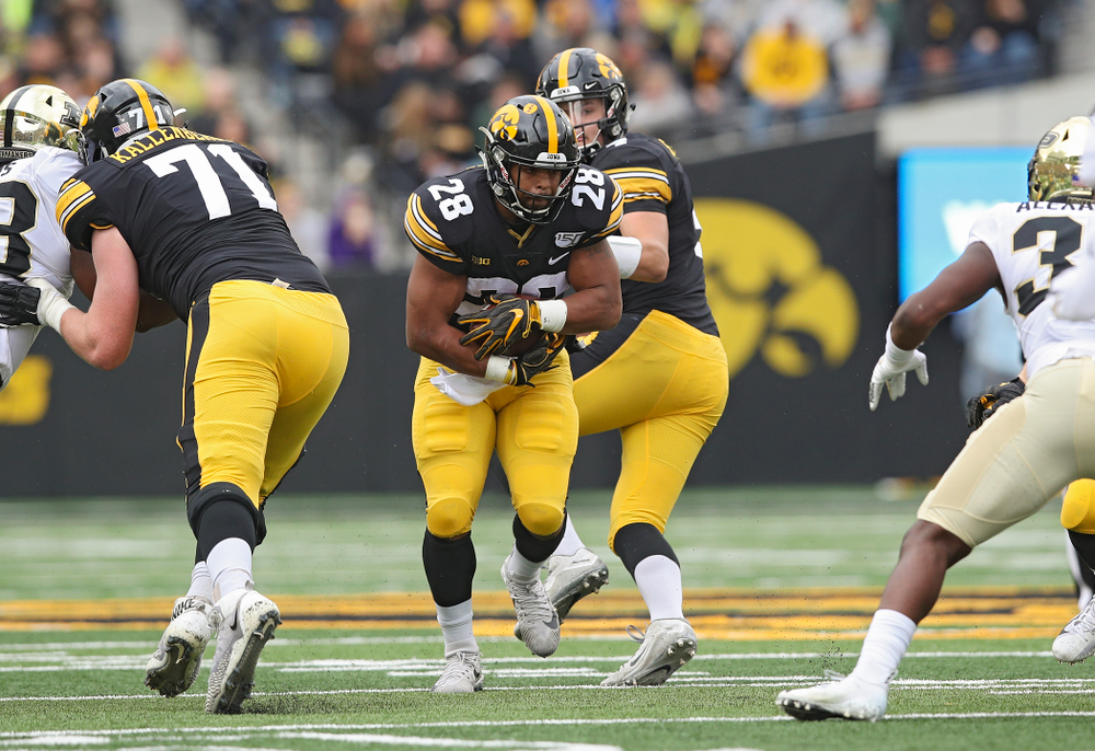 Iowa Hawkeyes running back Toren Young (28) takes a handoff from quarterback Nate Stanley (4) during the first quarter of their game at Kinnick Stadium in Iowa City on Saturday, Oct 19, 2019. (Stephen Mally/hawkeyesports.com)