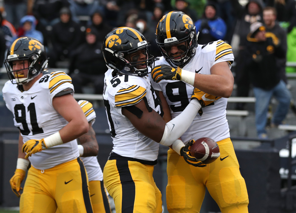 Iowa Hawkeyes defensive end A.J. Epenesa (94) celebrates with defensive end Chauncey Golston (57) after scoring against the Illinois Fighting Illini Saturday, November 17, 2018 at Memorial Stadium in Champaign, Ill. (Brian Ray/hawkeyesports.com)