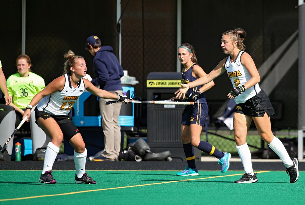 Iowa's Leah Zellner (13) hands Emily Deuell (2) her stick during the second quarter of their game at Grant Field in Iowa City on Friday, Sep 13, 2019. (Stephen Mally/hawkeyesports.com)