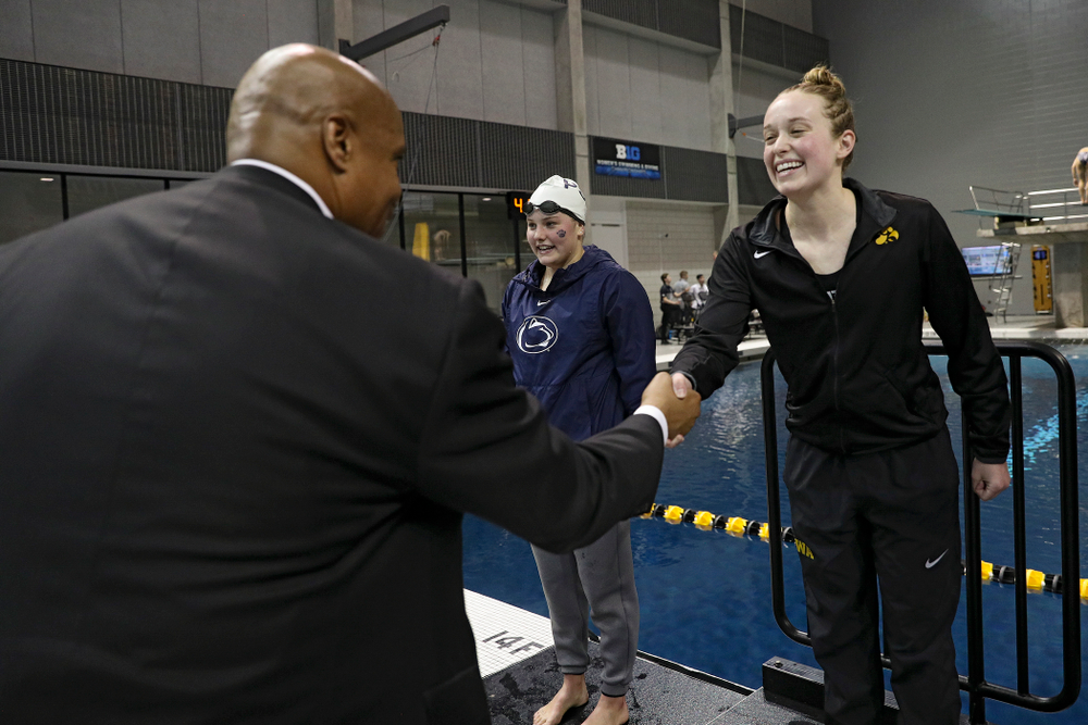 Iowa's Kelsey Drake (right) shakes hands with Big Ten Commissioner Kevin Warren after swimming the women's 100 yard butterfly final event during the 2020 Women's Big Ten Swimming and Diving Championships at the Campus Recreation and Wellness Center in Iowa City on Friday, February 21, 2020. (Stephen Mally/hawkeyesports.com)