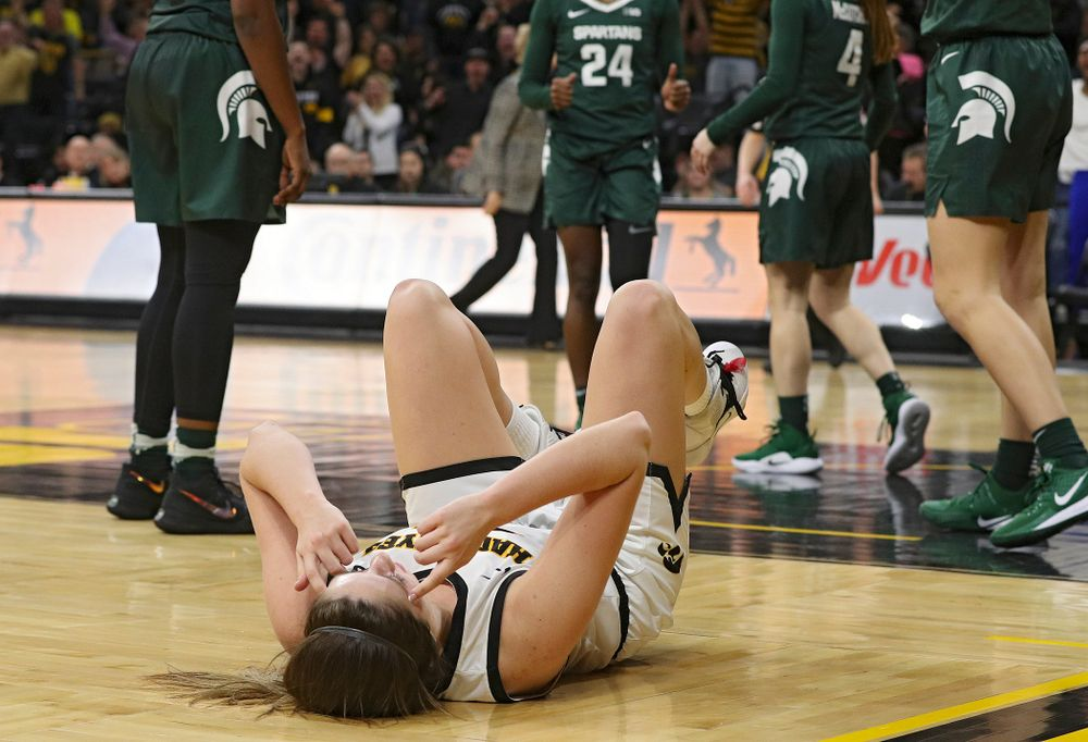 Iowa Hawkeyes guard Mckenna Warnock (14) points to her head as she celebrates after making a basket while being fouled during the fourth quarter of their game at Carver-Hawkeye Arena in Iowa City on Sunday, January 26, 2020. (Stephen Mally/hawkeyesports.com)