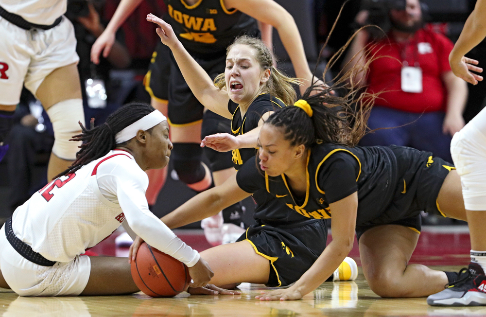 Iowa guard Kathleen Doyle (22) and guard Alexis Sevillian (5) battle for a loose ball during overtime of their game at the Rutgers Athletic Center in Piscataway, N.J. on Sunday, March 1, 2020. (Stephen Mally/hawkeyesports.com)