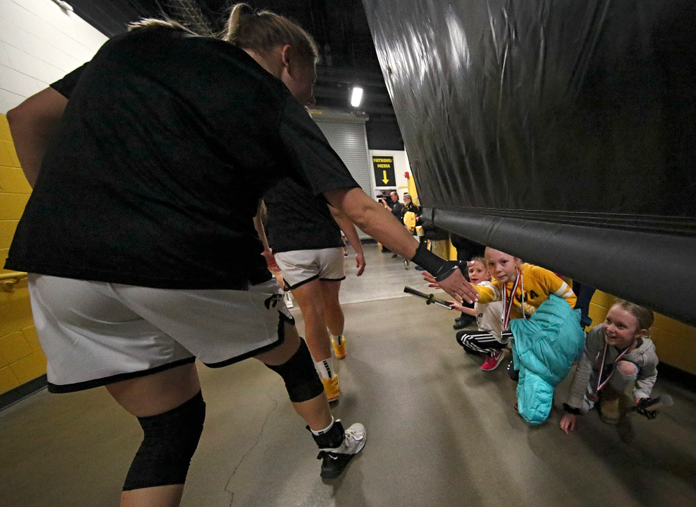 Young fans give Iowa Hawkeyes forward Monika Czinano (25) a high-five as she walks to the court before the start of their game at Carver-Hawkeye Arena in Iowa City on Sunday, January 26, 2020. (Stephen Mally/hawkeyesports.com)