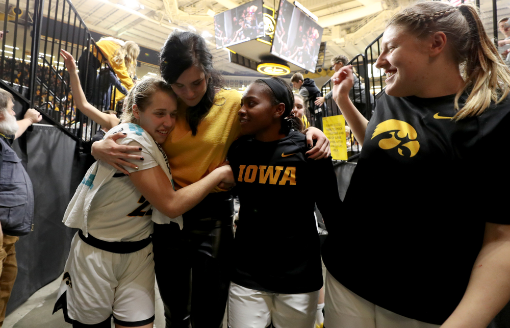 Megan Gustafson hugs Iowa Hawkeyes guard Kathleen Doyle (22) and guard Zion Sanders (21) following a jersey retirement ceremony Sunday, January 26, 2020 at Carver-Hawkeye Arena. (Brian Ray/hawkeyesports.com)