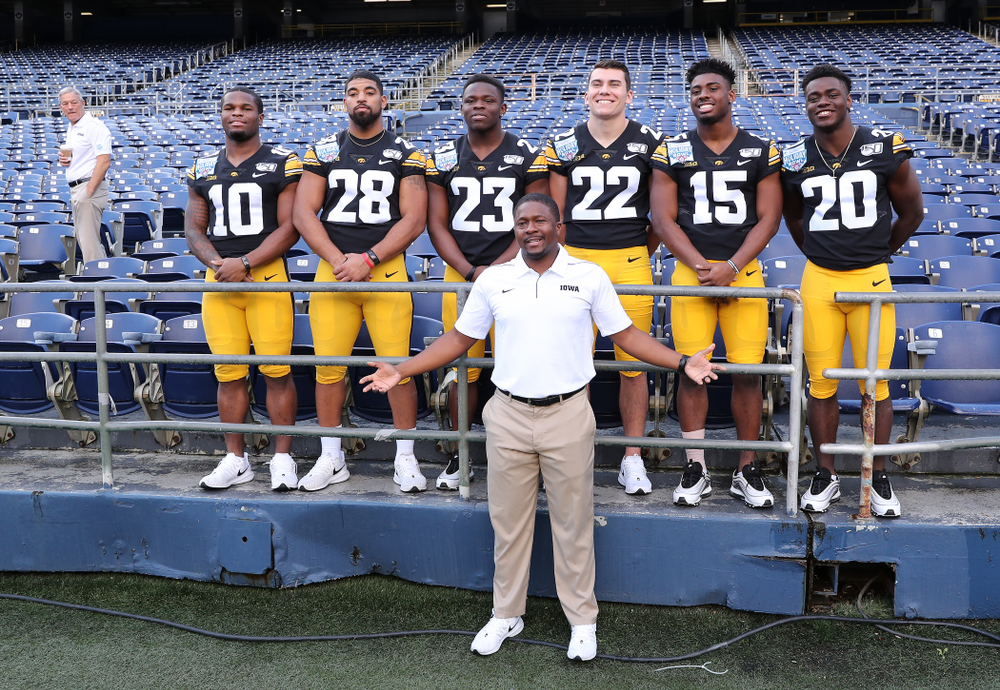 Iowa Hawkeyes running backs coach Derrick Foster with running backs Mekhi Sargent, Toren Young, Shadrick Byrd, Samson Evans, Tyler Goodson, and Keontae Luckett following the team photo Wednesday, December 25, 2019 at SDCCU Stadium in San Diego. (Brian Ray/hawkeyesports.com)