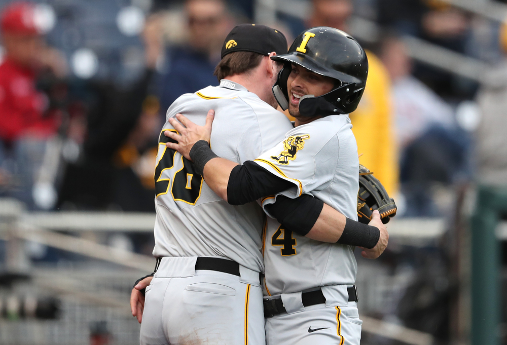 Iowa Hawkeyes infielder Mitchell Boe (4) hugs Chris Whelan (28) after scoring against the Indiana Hoosiers in the first round of the Big Ten Baseball Tournament Wednesday, May 22, 2019 at TD Ameritrade Park in Omaha, Neb. (Brian Ray/hawkeyesports.com)