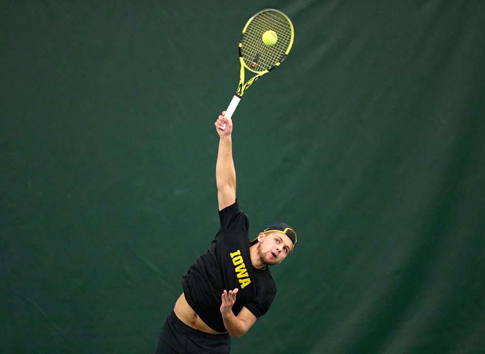 Iowa's Will Davies serves during their doubles match against Marquette at the Hawkeye Tennis and Recreation Complex in Iowa City on Saturday, January 25, 2020. (Stephen Mally/hawkeyesports.com)