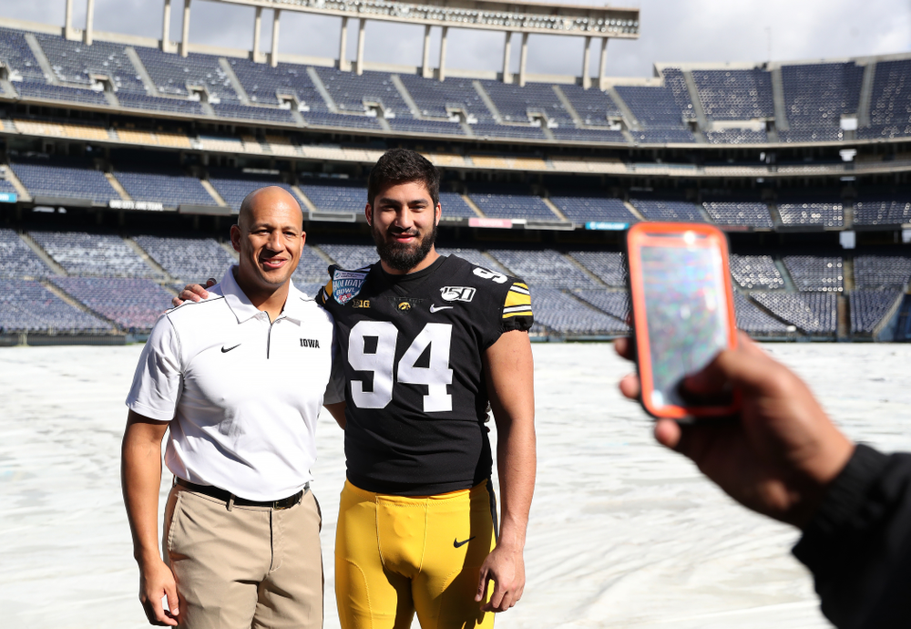 Iowa Hawkeyes special teams coordinator LeVar Woods  and defensive end A.J. Epenesa (94) following the team photo Wednesday, December 25, 2019 at SDCCU Stadium in San Diego. (Brian Ray/hawkeyesports.com)