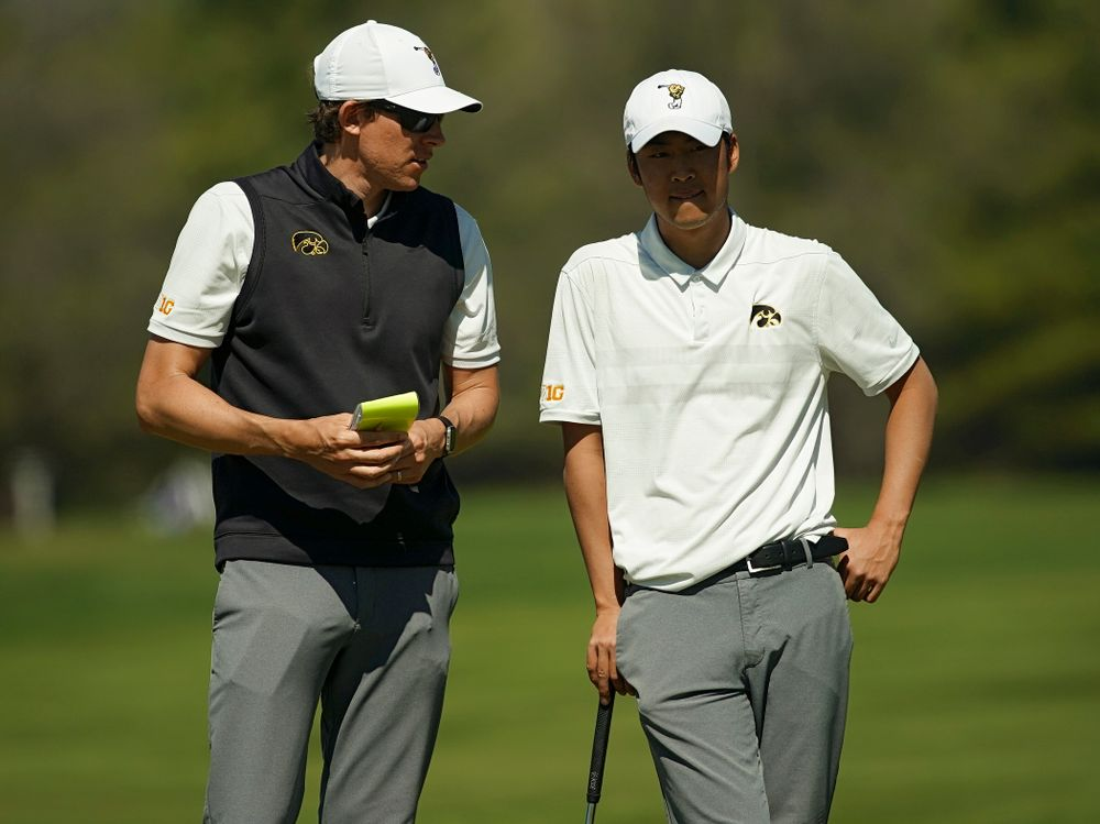 Iowa assistant coach Charlie Hoyle (from left) talks with Joe Kim during the second round of the Hawkeye Invitational at Finkbine Golf Course in Iowa City on Saturday, Apr. 20, 2019. (Stephen Mally/hawkeyesports.com)