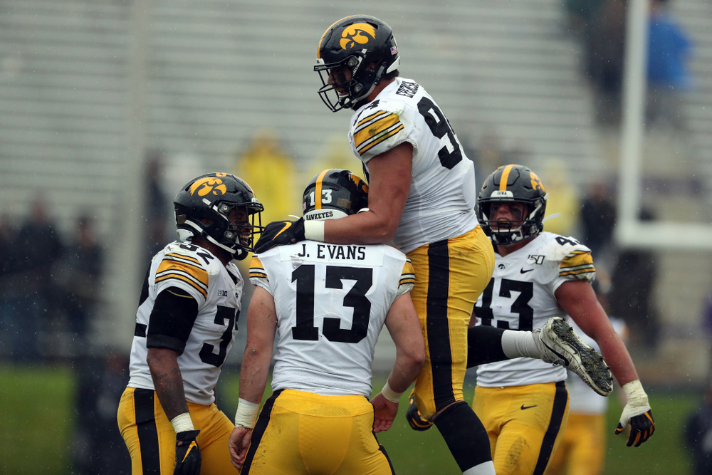 Iowa Hawkeyes linebacker Joe Evans (13) is congratulated by defensive end A.J. Epenesa (94) after recording his first career sack against the Northwestern Wildcats Saturday, October 26, 2019 at Ryan Field in Evanston, Ill. (Brian Ray/hawkeyesports.com)