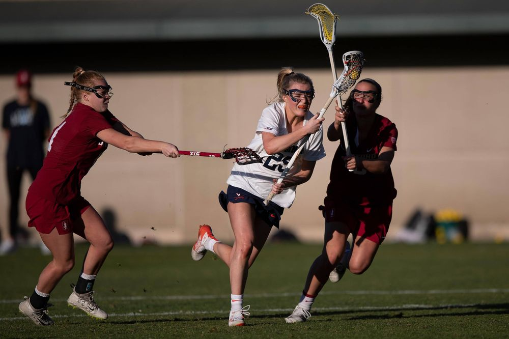 STANFORD, California - FEBRUARY 14:  Virginia Cavaliers midfield Courtlynne Caskin (25) is defended by Stanford Cardinal defense Maggie Bellaschi (11) and midfield Chelsea Trattner (16) during the second half at Cagan Stadium on February 14, 2020 in Stanford, California. The Virginia Cavaliers defeated the Stanford Cardinal 12-11. (Photo by Jason O. Watson)