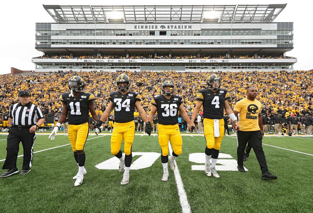 Iowa Hawkeyes captains defensive back Michael Ojemudia (11), linebacker Kristian Welch (34), fullback Brady Ross (36), and quarterback Nate Stanley (4) walk to the center of the field for the coin toss with honorary captain Miguel Merrick before their game at Kinnick Stadium in Iowa City on Saturday, Sep 28, 2019. (Stephen Mally/hawkeyesports.com)